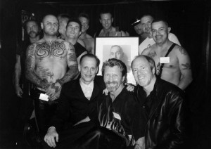 (seated L to R) John Waters, Durk Dehner anf Greg Gorman with men at the TOM House in front of Robert Maplwthorp's portrait of TOM.